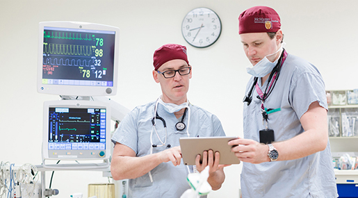 Two McMaster anesthesiologists consulting using a tablet computer