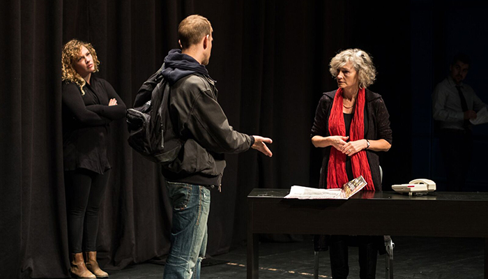 A psychiatrist, right with red scarf, listens to an actor playing a homeless person in a 2016 production of Gerbils