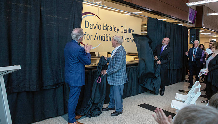 Paul O'Byrne, Mel Hawkrigg, and Gerry Wright unveil the sign at an opening celebration June 24, 2019.
