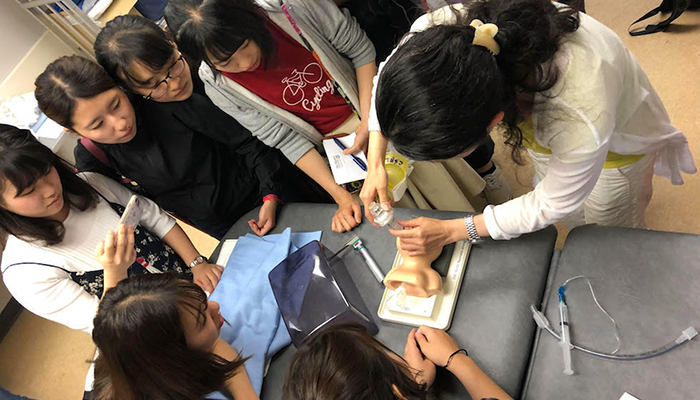 Dr. Noriko Nagao, associate professor from Kitasato University's School of Nursing, leads a hands-on learning exercise with delegation students at McMaster's Centre for Simulation Based Learning.