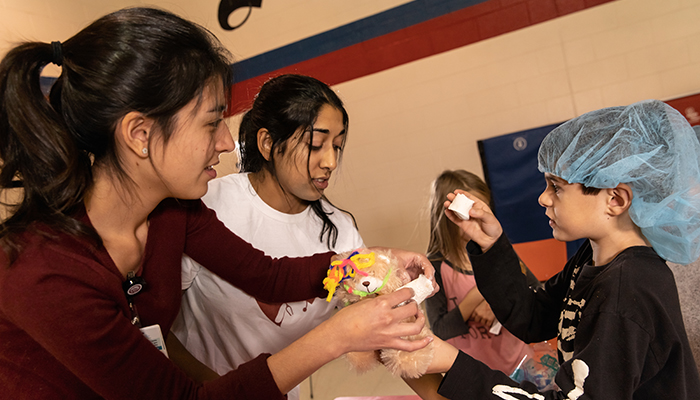 McMaster medical students Victoria Liu and Nisha Goel apply a cast to the teddy bear of Keegan Pearce, 9, at the Teddy Bear Clinic in Thorold.