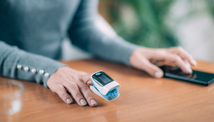 Patients use an oximeter to measure and report their blood oxygen saturation level