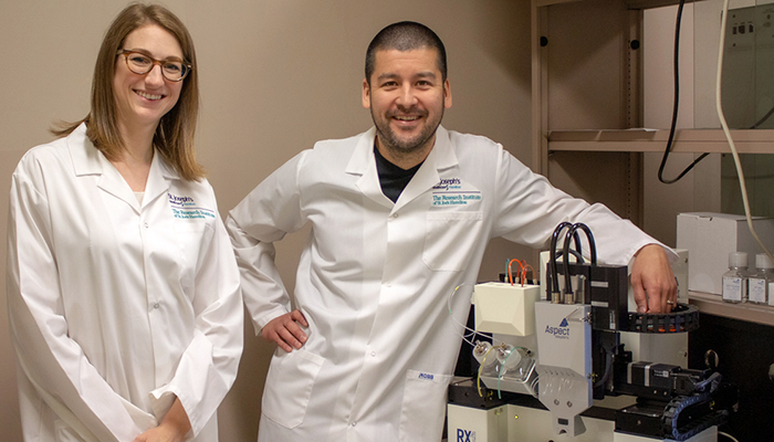 Erin Bedford (applications scientist, Aspect Biosystems) and Dr. Jeremy Hirota standing next to the Aspect Biosystems RX1™ 3D Bioprinter