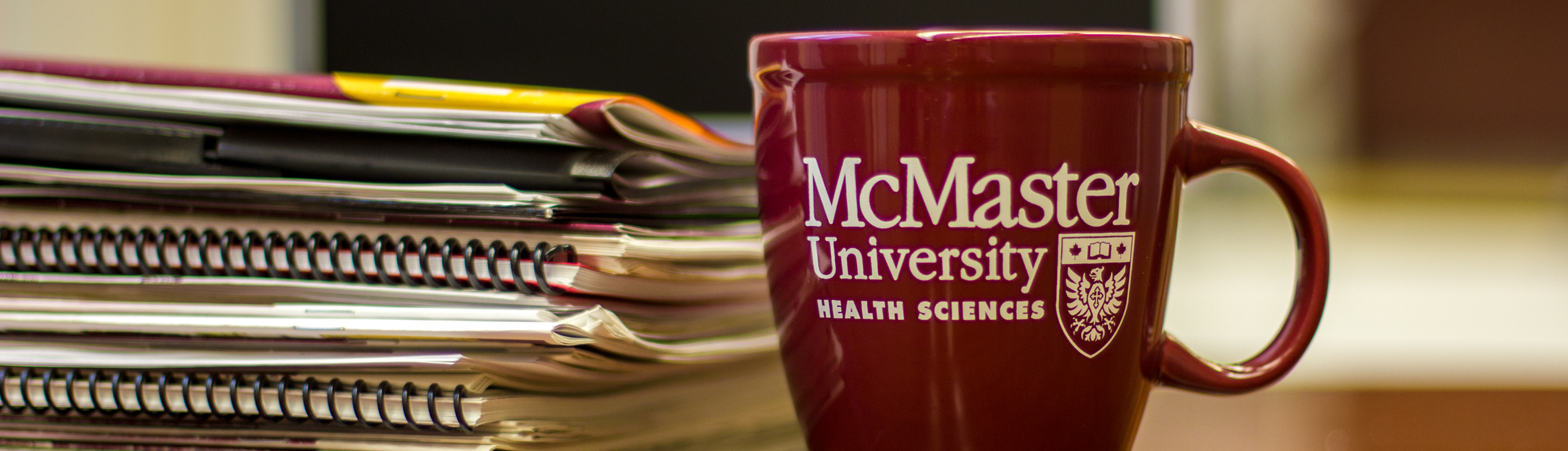 A stack of papers and a McMaster Health Sciences branded coffee cup.