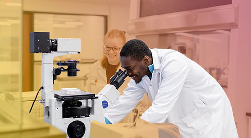 Two BioPharm students at a microscope