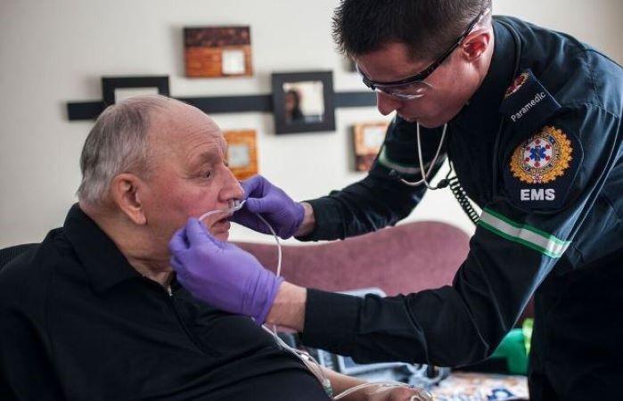 paramedics treating elderly patient