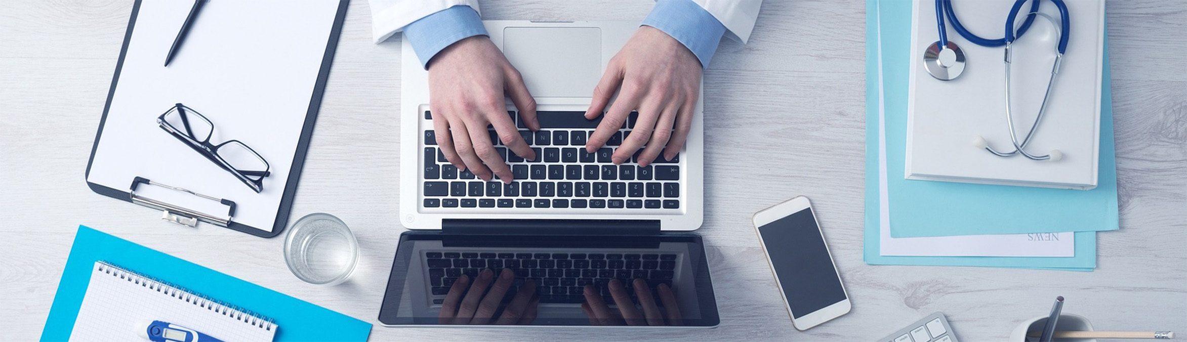 A doctors hands typing on a computer