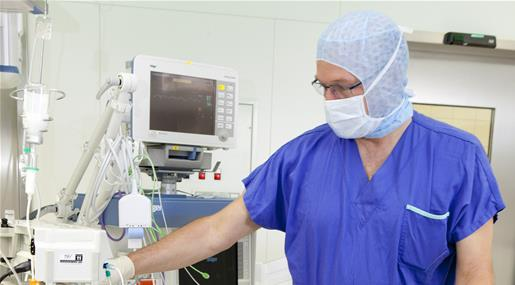 An anesthesiologist making an adjustment on a piece of equiptment